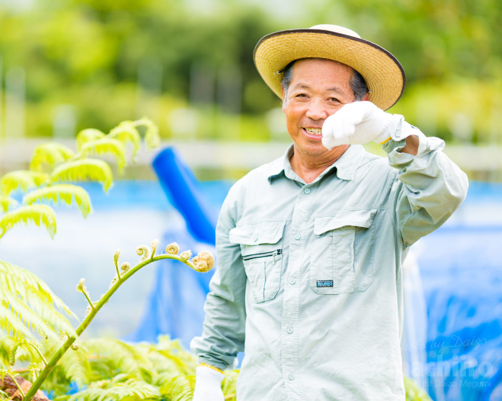 奄美フルーツファーム 農園で汗を拭う木村代表写真 1